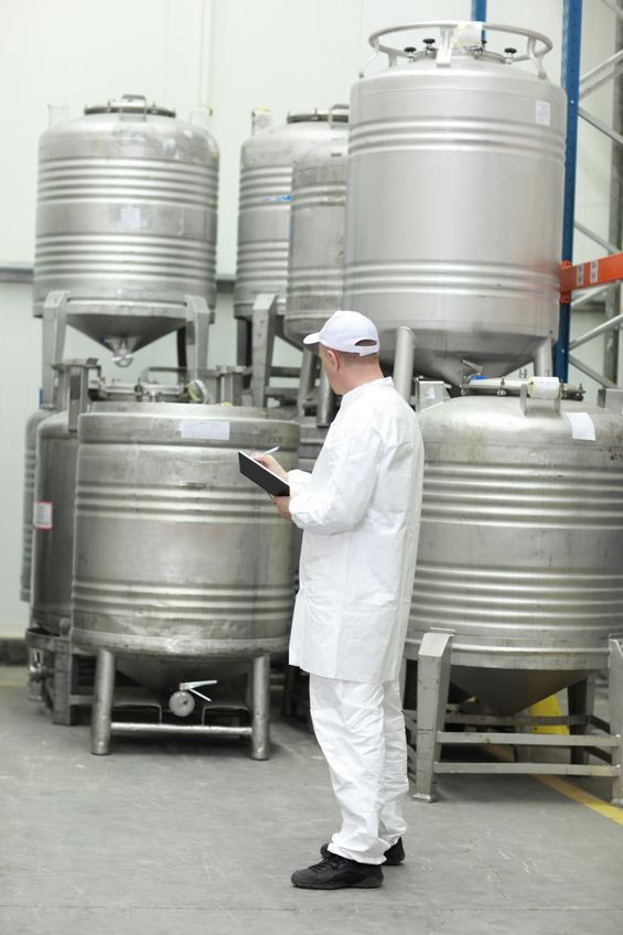 13234169 - worker in white uniform checking stocks in liquid foodstuff storehouse
